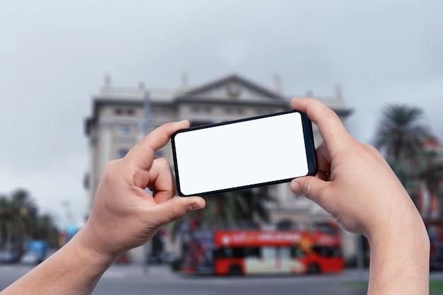 Maqueta del teléfono inteligente en las manos del hombre en la calle