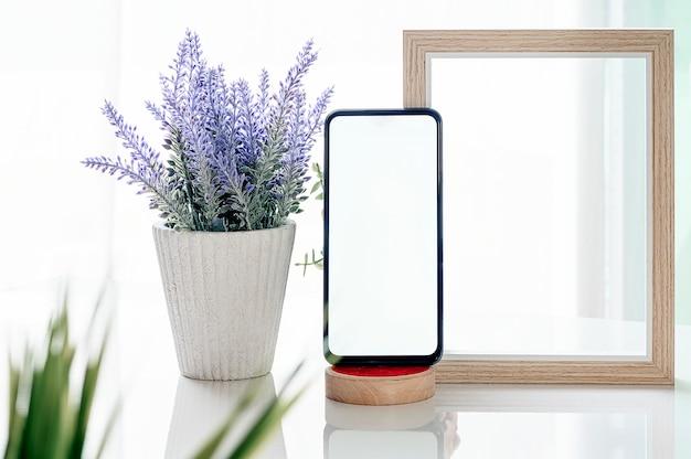Maqueta de teléfono inteligente con pantalla en blanco, marco de madera y planta de interior