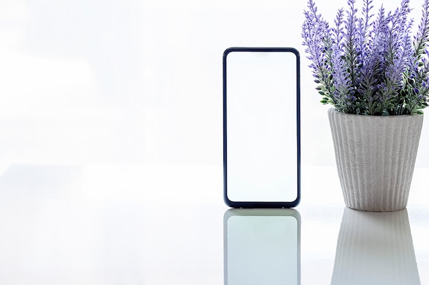Maqueta de teléfono inteligente con pantalla en blanco y planta de interior en la mesa superior blanca