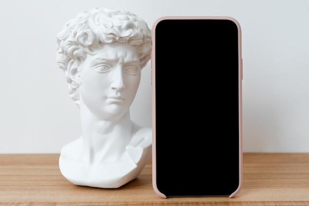Maqueta de teléfono inteligente con pantalla en blanco sobre mesa con escultura de busto pequeño