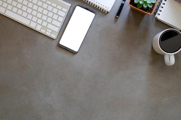 Maqueta de teléfono inteligente con pantalla vacía en el espacio de trabajo.
