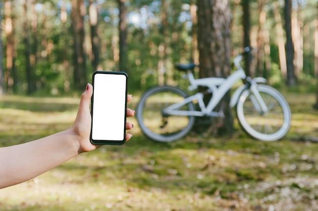 Maqueta de teléfono en la mano de la niña. en el contexto de la naturaleza en bicicleta y bosque.