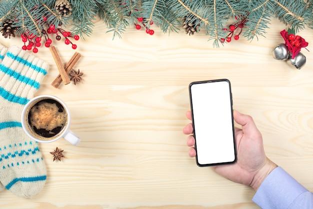 Maqueta de teléfono móvil en navidad. mano que sostiene el teléfono celular móvil de pantalla en blanco.