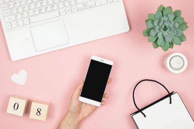Maqueta de teléfono móvil con pantalla en blanco copia espacio en mano femenina. flat lay home escritorio de oficina. espacio de trabajo femenino con manos femeninas, computadora portátil y accesorios en superficie rosa.