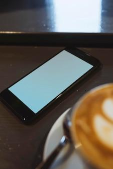 Maqueta de teléfono móvil con una taza de café
