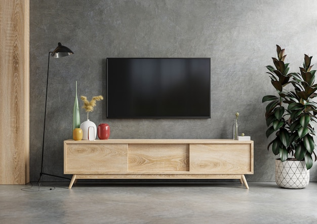 Maqueta de un televisor montado en la pared en una habitación oscura con una pared de hormigón. representación 3d