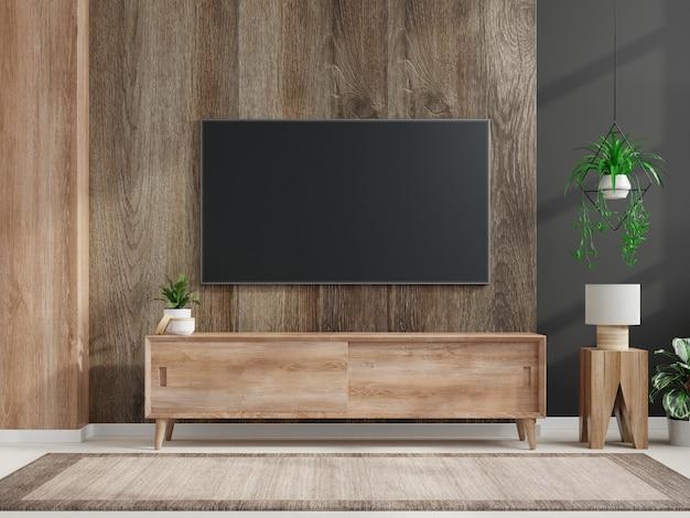 Maqueta de un televisor montado en la pared en una habitación oscura con una pared de madera oscura
