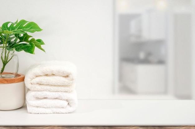 Maqueta de toallas blancas y planta de interior en la mesa blanca con espacio de copia para la visualización del producto.