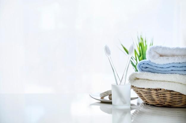Maqueta de toallas suaves en cesta y cepillo de dientes en blanco