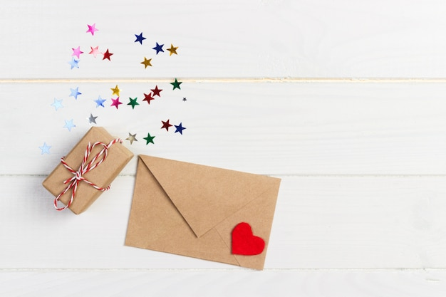 Maqueta de vacaciones: cajas de regalo, corazón rojo y papel en blanco en sobre marrón sobre fondo de madera blanco