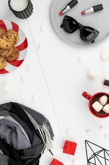 Maqueta de venta de compras navideñas con bufanda, cosméticos y gafas de sol sobre fondo de madera. plantilla plana de vista superior con espacio de copia