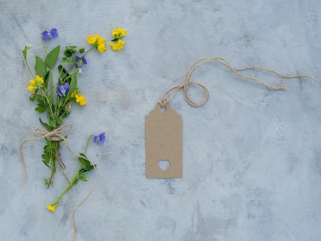 Maqueta vintage con flores de verano, una etiqueta vacía sobre fondo gris.