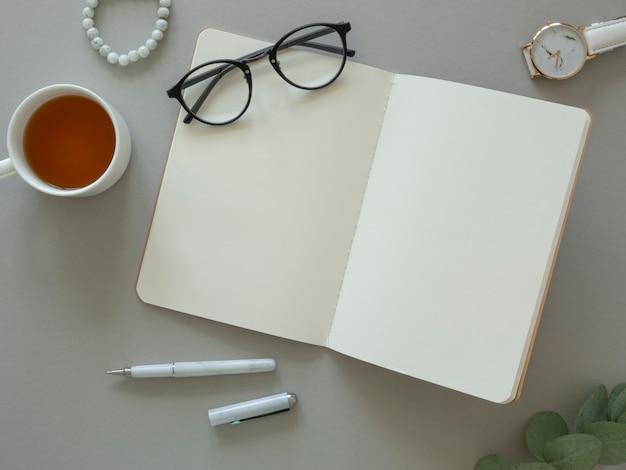 Maqueta de vista superior del espacio de trabajo femenino. gafas sobre un cuaderno abierto con espacio de copia y eucalipto