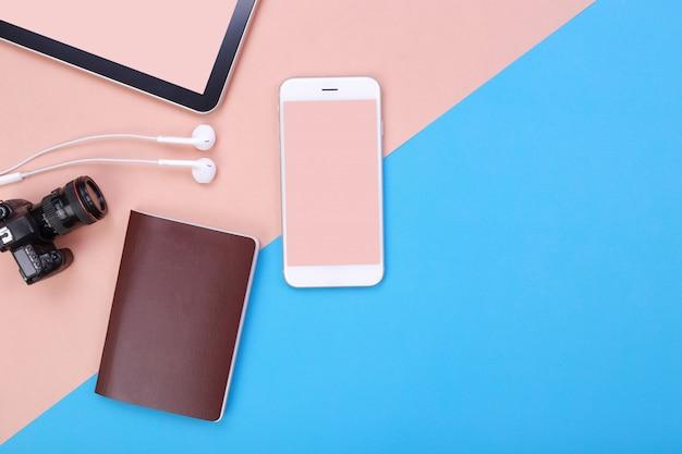 Maqueta de vista superior para smartphone con tableta y pasaporte sobre fondo rosa y azul pastel