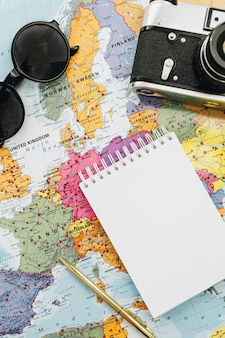 Maquetas de notas de viaje. mapa de europa, cámara, gafas de sol y cuaderno. endecha plana, vista superior