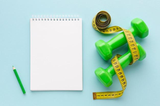 Maquetas de pesas verdes y cuaderno