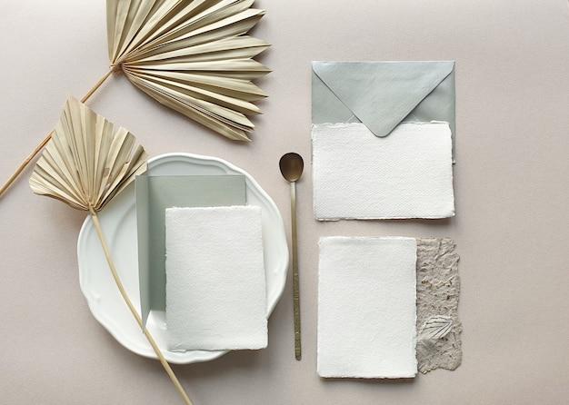 Maquetas de tarjetas de invitación de boda en blanco con hoja de palma seca y sobre artesanal sobre fondo de mesa con textura. elegante plantilla moderna para la identidad de marca. diseño tropical vista plana, vista superior