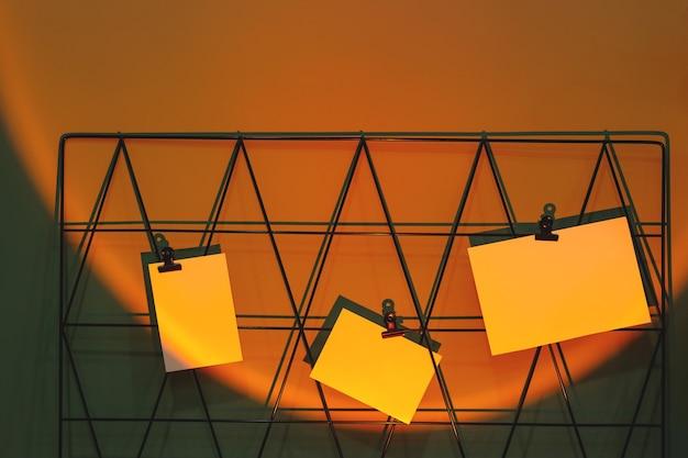 Maquetas de tarjetas en el moodboard con recordatorios en el lugar de trabajo independiente en la proyección de la lámpara al atardecer