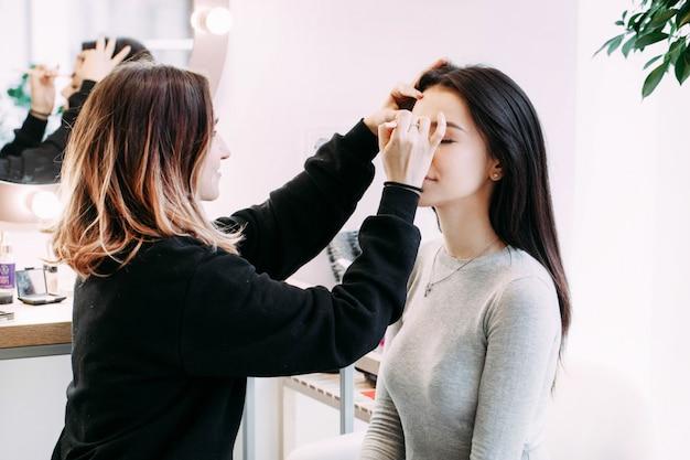 El maquillador hace las cejas de la señora que se sientan antes de ella