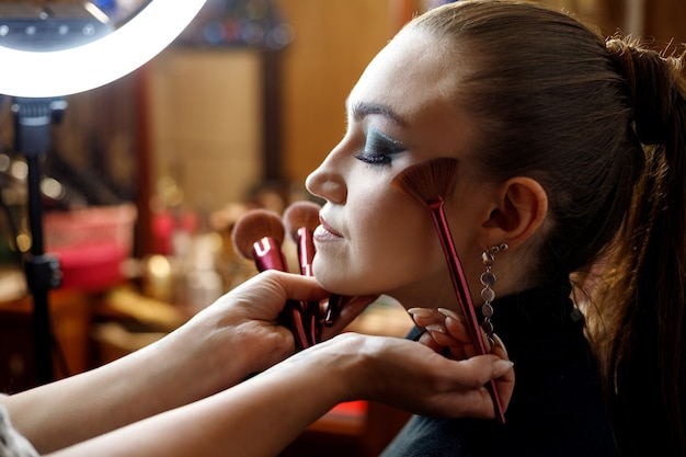 Un maquillador hace maquillaje para una hermosa joven en un salón de belleza.