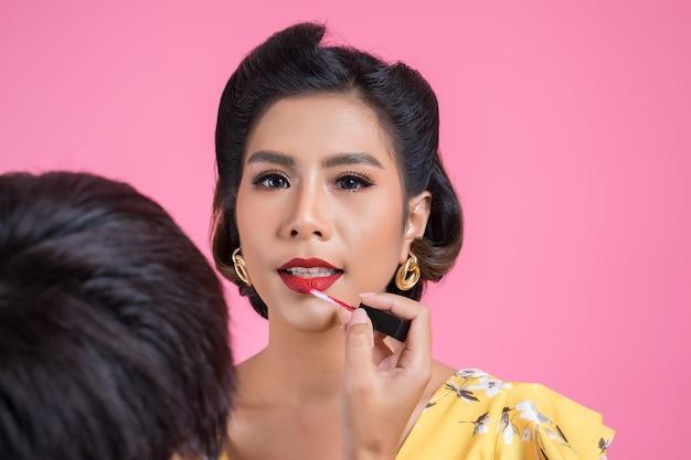 Maquillador haciendo maquillaje en cara de moda mujer.