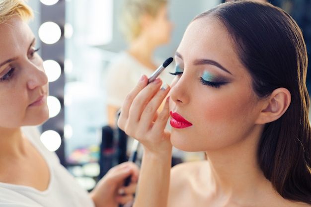 Maquillador haciendo maquillaje profesional de mujer joven.