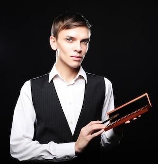 Maquillador masculino que se queda sobre un fondo oscuro, sosteniendo un pincel profesional y una paleta de sombras, mirando a la cámara, sugiriendo maquillarte.