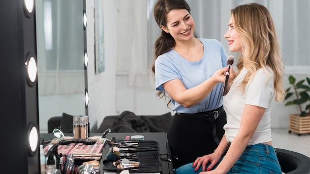 Maquillador pintando la cara de la rubia.