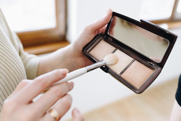 El maquillador profesional o mua está sosteniendo una paleta de cosméticos de sombra de ojos. ciérrese para arriba de la mano de la mujer caucásica con el espejo compacto y un cepillo para la aplicación de la sombra de ojos en cara.