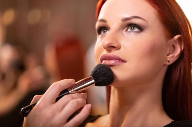 Maquilladora aplicando base tonal líquida en el rostro de la mujer