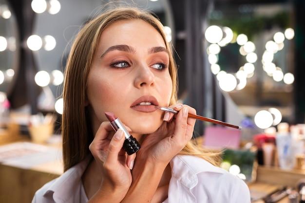Maquilladora aplicando lápiz labial en labios de mujer sonriente con pincel