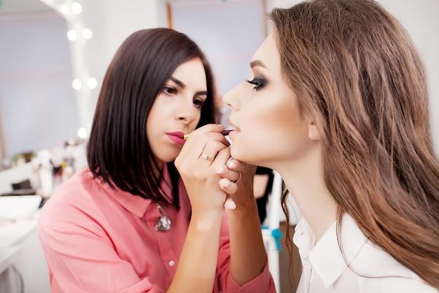 Maquilladora aplicando sombra de ojos de color base brillante en el ojo de la modelo y sosteniendo una concha con sombra de ojos