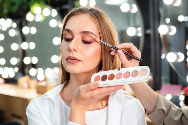 Maquilladora aplicando sombra de ojos a mujer con pincel