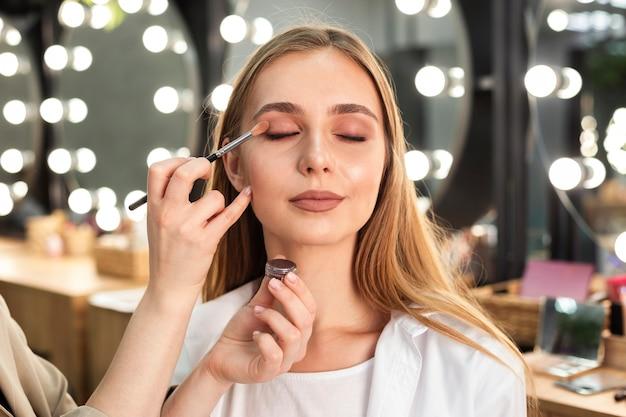Maquilladora aplicando sombra de ojos en mujer