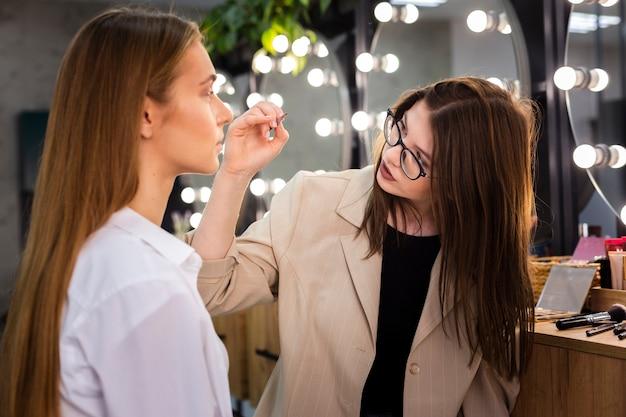 Maquilladora aplicando sombra de ojos con pincel sobre mujer
