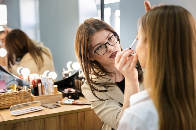 Maquilladora aplicando sombra de ojos