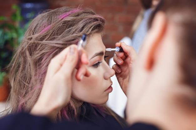 Maquilladora arreglando las cejas de la modelo con gel