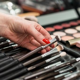 Maquilladora con colección de pinceles profesionales.