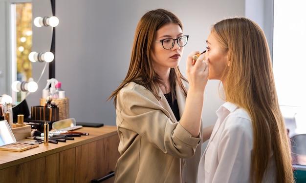 Maquilladora concentrada aplicando rimel en mujer