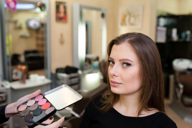 Maquilladora hace maquillaje de niña hermosa