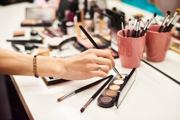Maquilladora haciendo un maquillaje perfecto para la joven modelo