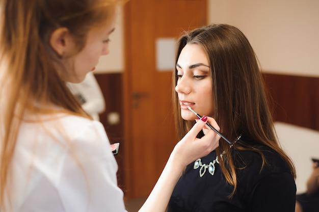 Maquilladora haciendo maquillaje profesional de mujer joven.
