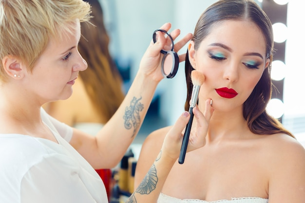 Maquilladora haciendo maquillaje profesional de mujer joven