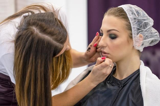 Maquilladora pinta los labios de una joven en un salón de belleza