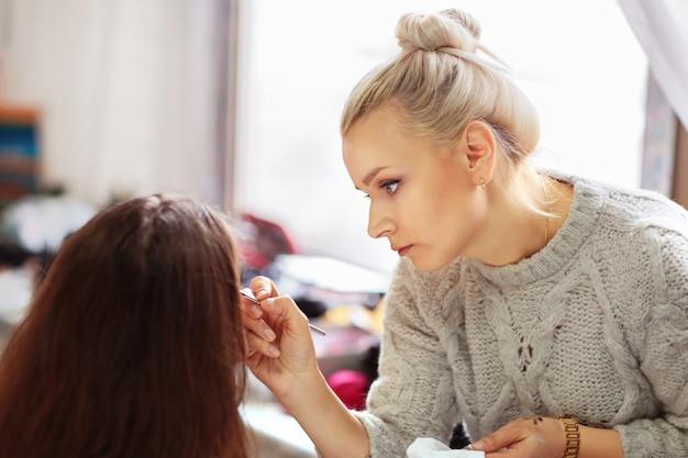 Maquilladora profesional aplica maquillaje a chicas guapas para las vacaciones.