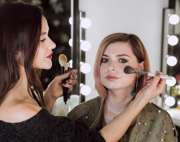 Maquilladora profesional trabajando tiro medio