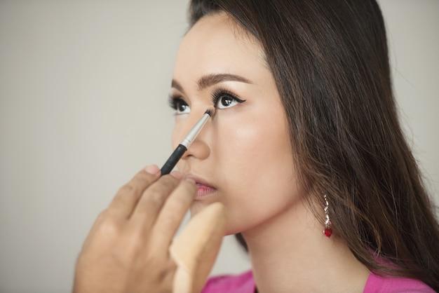 Maquilladora en el trabajo. modelo de moda de mujer de asia maquillaje