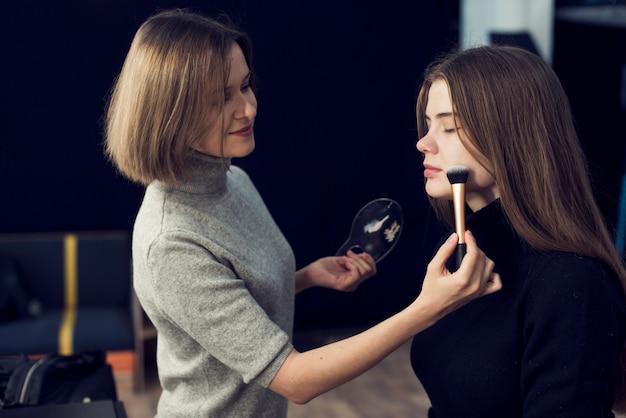 Maquilladora de vista lateral aplicando polvo en modelo