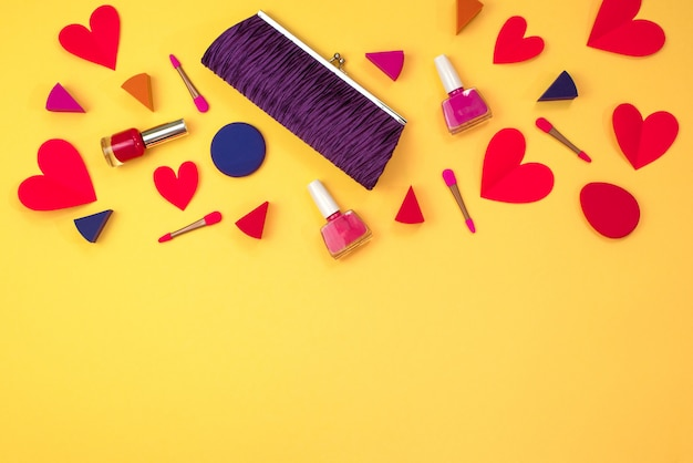 El maquillaje de los accesorios de mujer es el bolso corazón rojo sobre fondo amarillo.
