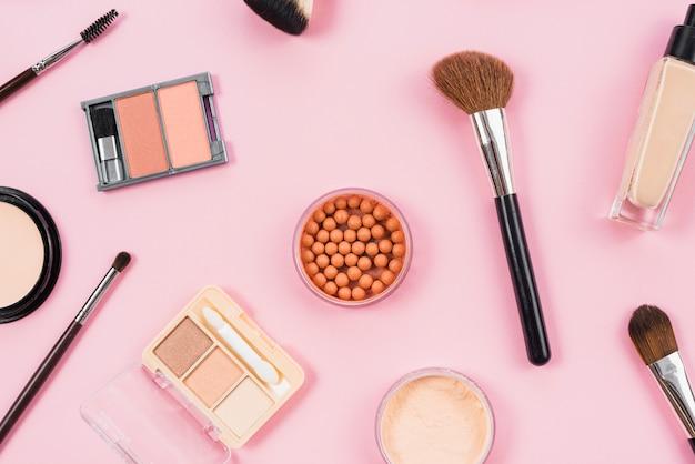 Maquillaje y arreglo de accesorios cosméticos sobre fondo rosa.